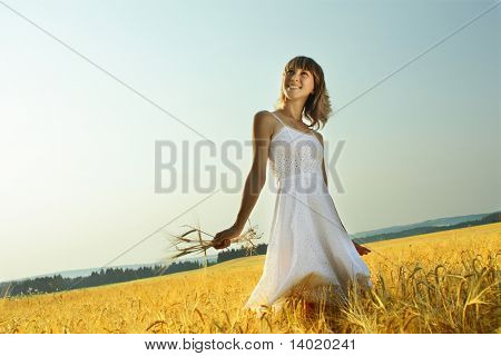 Young woman in white dress standing in field with wheat
