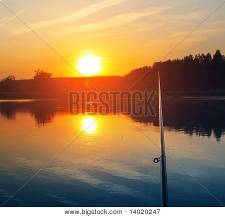 Fishing rod sunset and bobber on water