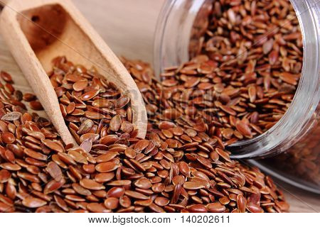 Heap of brown linseed flax seeds spilling out of glass jar on wooden background concept of healthy nutrition