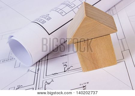 House Of Wooden Blocks And Rolls Of Diagrams On Construction Drawing Of House