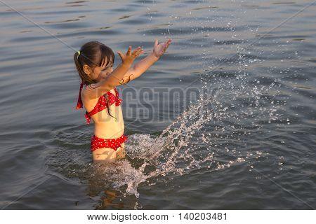 little white girl children make water splashes on lake