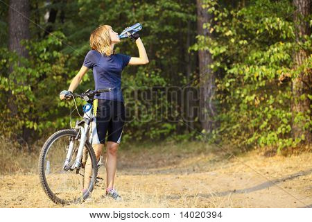 Young woman with bike drinking water from bottle
