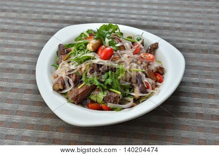 Vegetables mix salad with mushroom tomato and herbs on white plate in asian restaurant
