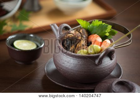 Black pot of shrimp and mushroom and herbs on the table
