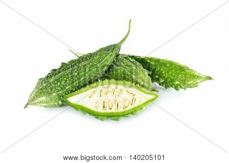 whole and half cut fresh bitter gourd on white background