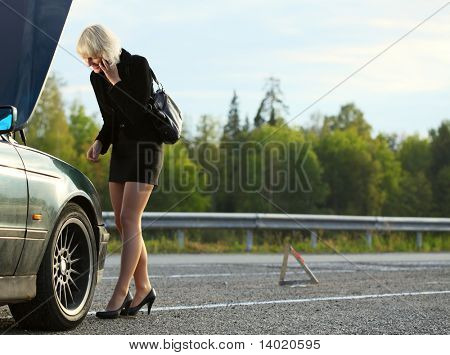 Young woman talking on mobile phone near broken car