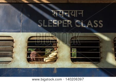 Gokarna, India - January 14, 2016: Unidentified passenger of the Indian Railway looking in the window of the train at Gokarna road station, India.