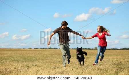 Young couple running together on meadow with dog