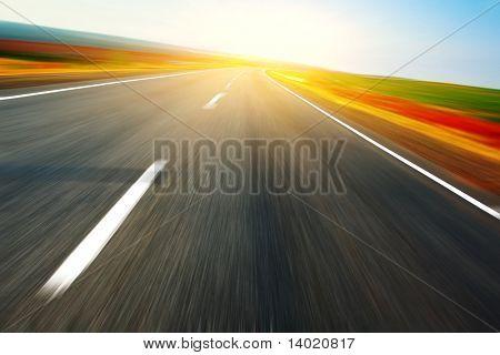 Blurred asphalt road and blue sky with light spot