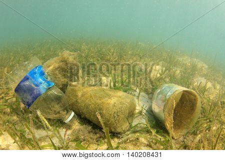 Plastic pollution in ocean. Water bottles and bags thrown into sea causing environmental problems.