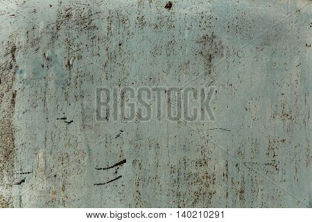 Old rusty metal surface is covered with white paint with scratches and stains. background