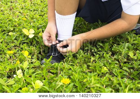 Childs student  tying shoes in the park of school.