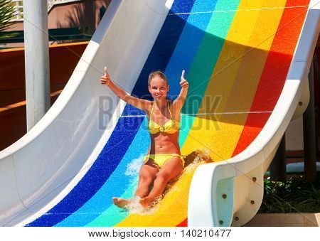 Nice beautiful girl on water slide at water park show thumb up. Water slides with flowing water in water park. Summer water park holiday. Outdoor in hot summer.