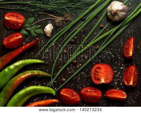 Composition with vegetables and spices on black kitchen table