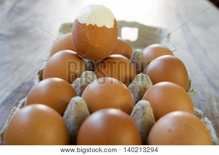 hardboiled egg partly shelled on a series of raw eggs