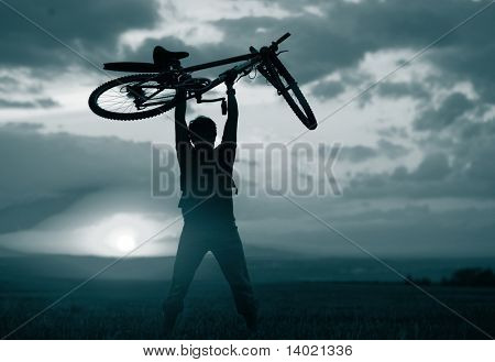 Man with bicycle lifted above him. Blue gray toned