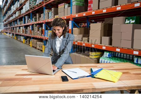 Business woman typing on her laptop in a warehouse