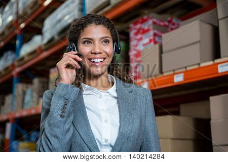 Business woman calling with her headset in a warehouse