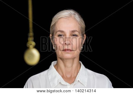 Senior woman being hypnotized with pendulum against black background