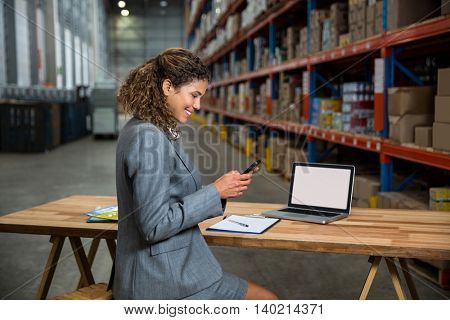 Business woman using her phone in a warehouse