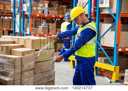 Worker opening a plastic for the boxes in a warehouse