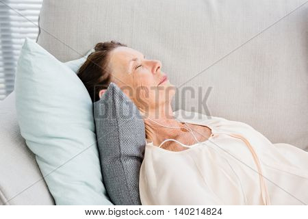 Mature woman listening to music while lying on sofa at home