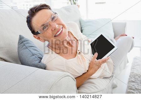 Portrait of smiling mature woman holding digital tablet while resting on sofa at home