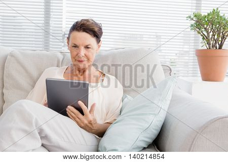 Confident mature woman using digital tablet while sitting on sofa at home