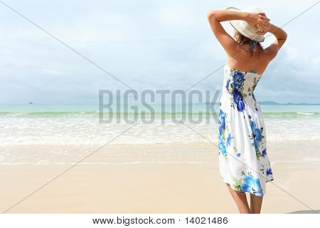 Young woman in dress holding a straw hat and looking to a blue sky