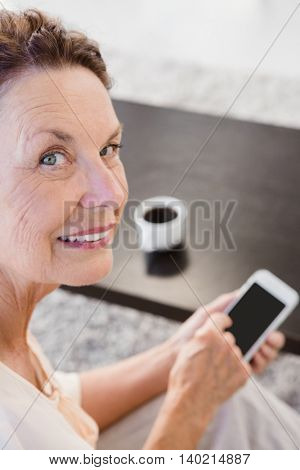 Portrait of cheerful mature woman holding smartphone while resting on sofa at home