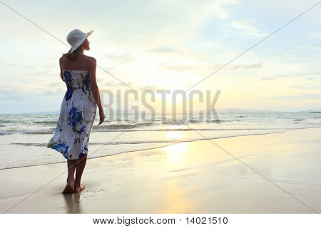 Young woman in hat standing on sand and looking to a sky