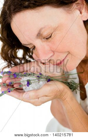 Smiling mature woman smelling flowers while standing at spa