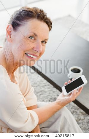 Portrait of happy mature woman holding smartphone while resting on sofa at home