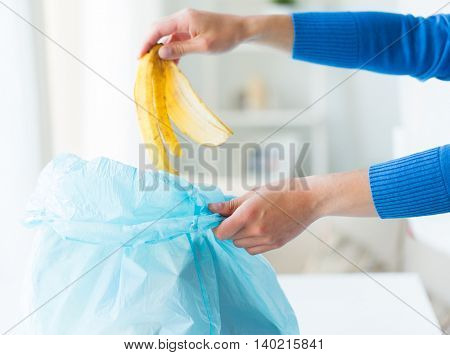 recycling, food waste, garbage, environment and ecology concept - close up of hand putting banana peel into rubbish bag at home