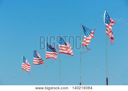 Five American flags blowing in the wind on blue sky
