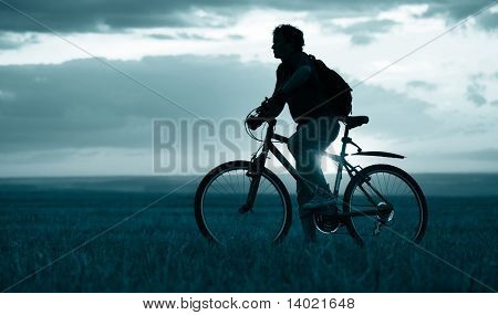 Man with bicycle standing on field on sunset background