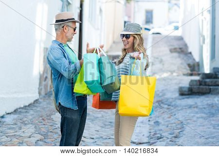 Happy mature couple holding shopping bags on street