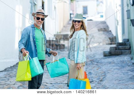 Portrait of mature couple holding shopping bags on street
