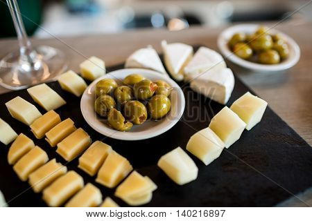 High angle view of cheese slices and olives on tray at restaurant