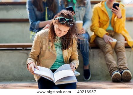 education, high school and people concept - high school student girl reading book outdoors