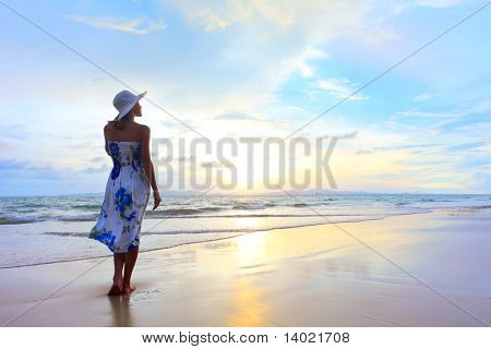 Young woman in straw hat standing on wet sand and looking to somewhere