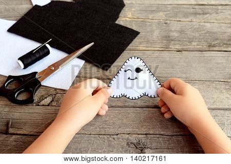 Child holds a felt ghost toy in his hands. Felt sheets, scissors, thread on an old wooden table. Felt Halloween ghost ornament. Halloween sewing crafts idea