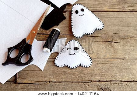 Cute little white ghosts crafts, felt sheets, scissors, thread, needles on an old wooden background. Easy Halloween felt pattern ghosts. Halloween sewing project for children