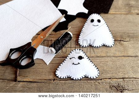 Handmade Halloween ghost doll. Two little felt ghosts, felt scraps, scissors, thread, pins, needles on an old wooden background. Funny Halloween characters
