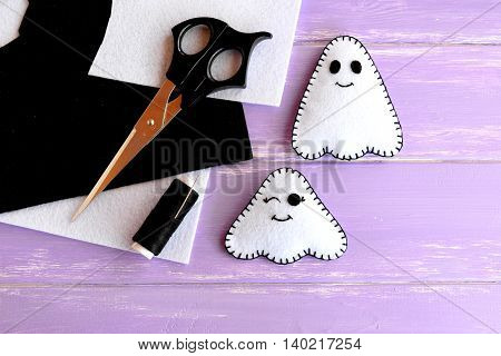 Two small white ghosts crafts, felt sheets, scissors, thread, needle on lilac wooden background. Hand Halloween decor idea for kids. Halloween sewing craft