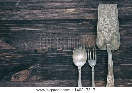 Antique cutlery on a wooden background: spoon fork spatula serving