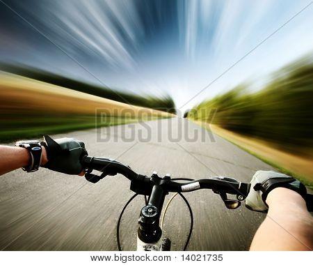 Rider fiets rijden op een asfaltweg. Beweging wazig achtergrond