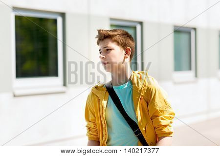 education, high school and people concept - teenage student boy walking outdoors