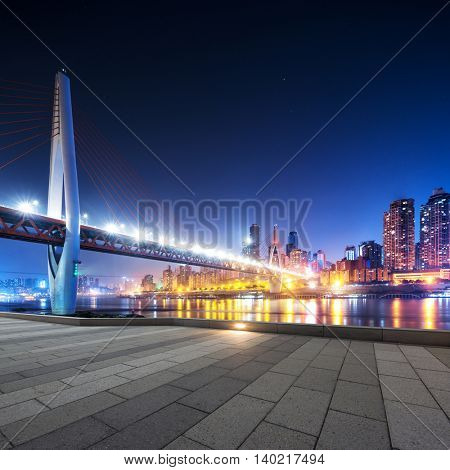 cityscape and skyline of downtown near bridge of chongqing at night from empty floor