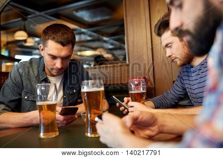 people, men, leisure, friendship and communication concept - male friends with smartphones drinking draft beer at bar or pub